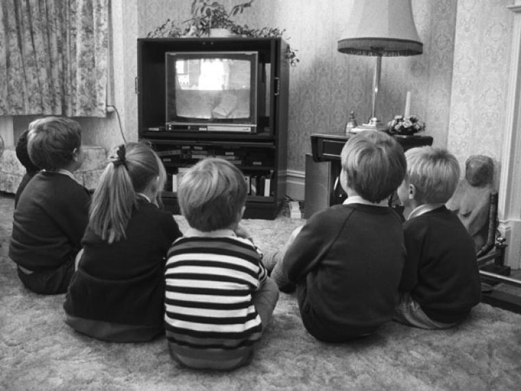 niños mirando una película en una televisión antigua